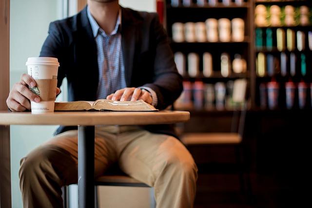 muž s kávou a knihou